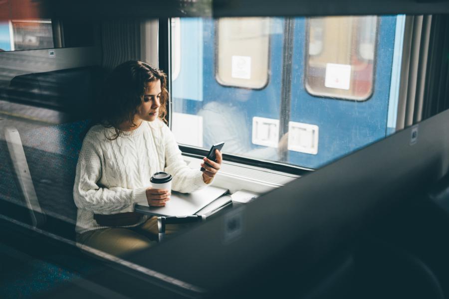 woman on train drinking coffee using mobile phone