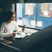 woman on train drinking coffee using mobile phone
